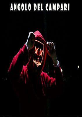 Un immagine scura, con un individuo che indossa una felpa rossa con cappuccio e dei guanti.  I pugni chiusi sono alzati all'altezza delle tempie ed in faccia indossa una maschera nera con gli occhi barrati ed illuminati da un led rosso cosi come la bocca.